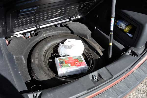 Place Toilet Paper Bag into Trunk of Car with Spare Tire